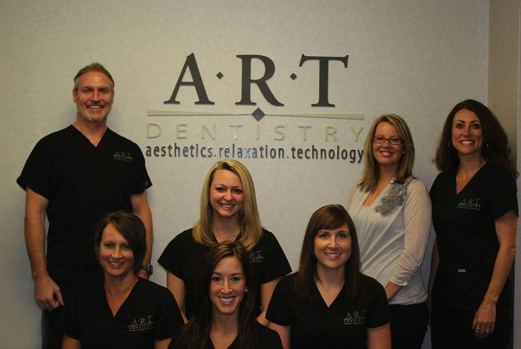 Dr. Martin with his dental team in front of logo